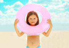 Little girl child with inflatable circle on the beach over sky Royalty Free Stock Photo