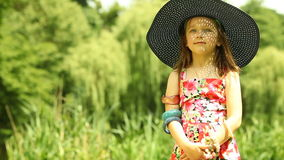 Little girl child kid putting on straw hat outdoor Stock Images