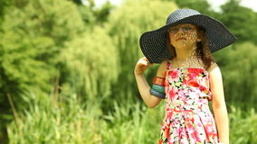 Little girl child kid taking straw hat off on the meadow Stock Photos