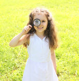 Little girl child looking through a magnifying glass on nature Royalty Free Stock Image