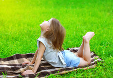 Little girl child lying on the grass does yoga exercise Royalty Free Stock Photo