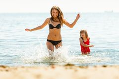 Little girl kid and woman mother in sea water. Fun stock photos