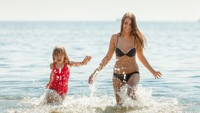 Little girl kid and woman mother in sea water. Fun stock images