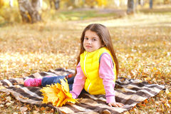 Little girl child on plaid with yellow maple leafs in autumn Stock Photos