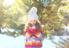 Little girl child playing blowing snow on hands in winter Stock Images