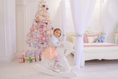 Little girl child playing in children`s room on pink background. Sweet girl baby swinging on rocking horse toy, smiling and looking at camera. Little blonde girl Stock Images