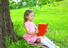 Little girl child reading a book on the grass near tree. In summer day Stock Image