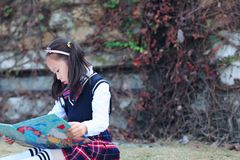 Little girl Child reading a book on the grass. Little girl Child Wearing a student suit reading a book on the grass in autumn city park Royalty Free Stock Photos