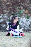 Little girl Child reading a book on the grass. Little girl Child Wearing a student suit reading a book on the grass in autumn city park Royalty Free Stock Photography