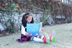 Little girl Child reading a book on the grass. Little girl Child Wearing a student suit reading a book on the grass in autumn city park Royalty Free Stock Images