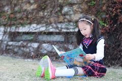 Little girl Child reading a book on the grass. Little girl Child Wearing a student suit reading a book on the grass in autumn city park Stock Photo
