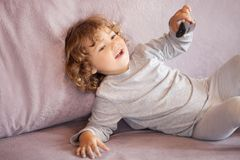 Toddler kid watching tv cartoons. Little girl child with remote control watching tv set in room stock photos