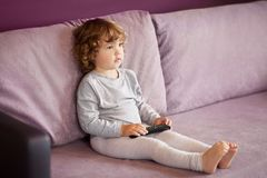Toddler kid watching tv cartoons. Little girl child with remote control watching tv set in room stock image