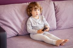 Toddler kid watching tv cartoons. Little girl child with remote control watching tv set in room royalty free stock photos