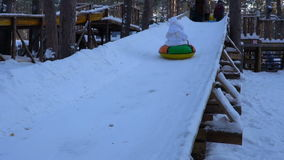 Little girl child rides a tube on an icy hill. The girl really like to ride on an inflatable sled. Girl laughs and emotes from the. Rapid descent from a hill stock video footage