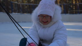Little girl child riding a toboggan. Girl really like to ride on the toboggan. Girl laughs and emotes from the fast toboggan rides stock video footage
