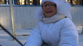 Little girl child riding a toboggan. Girl really like to ride on the toboggan. Girl laughs and emotes from the fast toboggan rides stock video