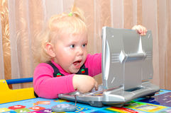 Little girl with child's computer (notebook). Royalty Free Stock Images