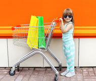 Little girl child and shopping cart with bags Stock Photography