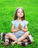 Little girl child sitting on the grass does yoga exercise Royalty Free Stock Photography