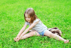 Little girl child sitting on the grass does yoga stretching Stock Image
