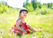 Little girl child sitting on the grass outdoors enjoying Stock Image