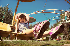 Little girl child sitting on a revolving carousel royalty free stock photo