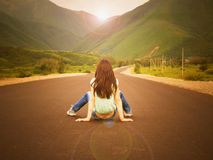 Little girl child sitting on the road to mountains at sunset Royalty Free Stock Photos