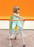 Little girl child sitting in shopping cart with bags Stock Photos