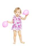 Little girl child standing holding balloons. Kid w Stock Image