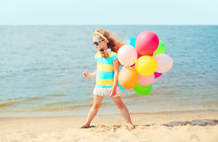 Little girl child on summer beach playing with colorful balloons Royalty Free Stock Image