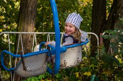 Little girl child swinging on a swing in an amusement park Royalty Free Stock Photo