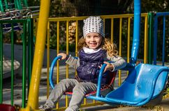 Little girl child swinging on a swing in an amusement park Royalty Free Stock Images