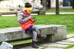 Little girl child using a mobile phone in public park. Instead of playing outside, child is playing games on telephone, sitting in granite bench. Children Stock Photos