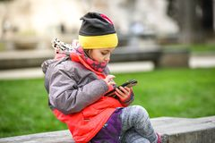 Little girl child using a mobile phone in public park. Instead of playing outside, child is playing games on telephone, sitting in granite bench. Children Stock Image