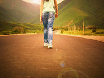 Little girl child walking on road to mountains at sunset royalty free stock photo