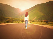 Little girl child walking on road to mountains at sunset royalty free stock image
