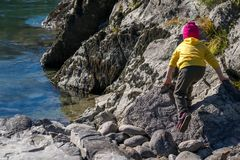 A child, in warm clothes and a red hat climbs the rocky Bank of the river stock photos