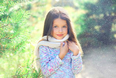 Little girl child wearing a scarf and sweater near christmas tree Stock Image
