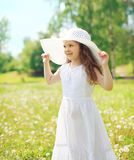 Little girl child wearing a straw hat and white dress in summer Royalty Free Stock Images