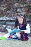 Little girl Child reading a book on the grass. Little girl Child Wearing a student suit reading a book on the grass in autumn city park Royalty Free Stock Image