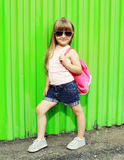 Little girl child wearing a t-shirt and sunglasses with backpack Royalty Free Stock Photo