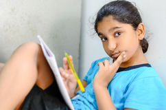 Little Girl child writing & reading Looking at camera Royalty Free Stock Photo