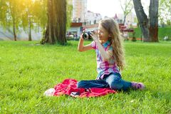 Little girl child of 8 years looking at camera sitting on green lawn in city park. stock images