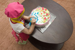 Little girl children decorate cream cake. On table Royalty Free Stock Photography