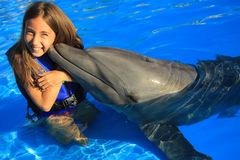Little girl children kissing a gorgeous dolphin flipper smiling face happy kid swim bottle nose dolphins. At aquarium high quality picture royalty free stock images