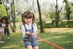 Little girl children playing tug of war at the park stock image