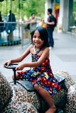 Little girl in children`s playground, driving the toy car. Enjoying the game Stock Images