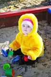 Little girl on a children's playground plays sand. The little girl on a children's playground plays sand in the autumn Royalty Free Stock Photo