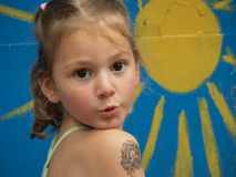 Little girl with a children`s tattoo on her forearm on the background of the painted sun stock image